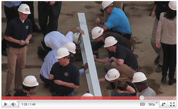 Builders, architects, engineers, steelworkers, and researchers sign cantilevered steel beam